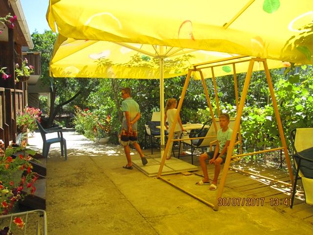 Детские качели у домиков в летнем саду